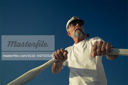 Croatia, Senior man with captain's hat steering sailboat Stock Photo - Premium Royalty-Free, Image code: 6115-06733320