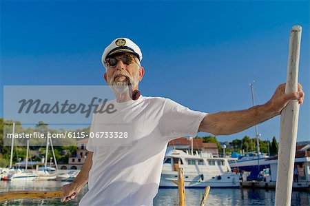 Croatia, Senior man with captain's hat on sailboat Stock Photo - Premium Royalty-Free, Image code: 6115-06733328