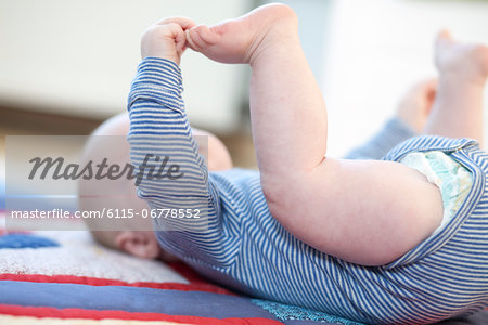 Baby boy lying on back, Munich, Bavaria, Germany Stock Photo - Premium Royalty-Free, Image code: 6115-06778552