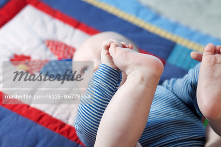 Baby boy lying on back, Munich, Bavaria, Germany Stock Photo - Premium Royalty-Free, Image code: 6115-06778554