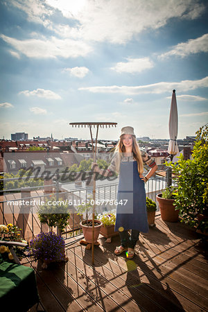 Young Woman On Balcony Holding Garden Rake, Munich, Bavaria, Germany, Europe Stock Photo - Premium Royalty-Free, Image code: 6115-06778647