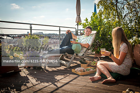 Couple Relaxing On Roof Terrace, Munich, Bavaria, Germany, Europe Stock Photo - Premium Royalty-Free, Image code: 6115-06778656