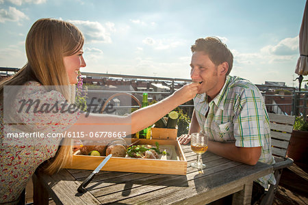 Woman Feeding Man On Balcony, Munich, Bavaria, Germany, Europe Stock Photo - Premium Royalty-Free, Image code: 6115-06778663