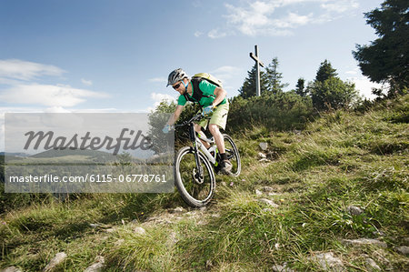 Mountain biker riding downhill, Samerberg, Germany Stock Photo - Premium Royalty-Free, Image code: 6115-06778761