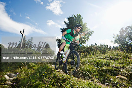 Mountain biker riding downhill, Samerberg, Germany Stock Photo - Premium Royalty-Free, Image code: 6115-06778762