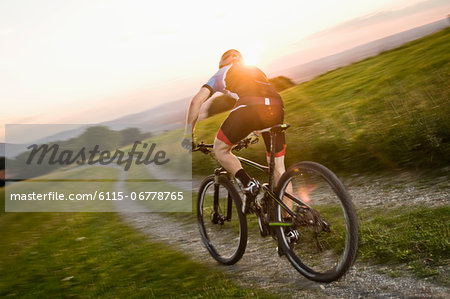 Mountain biker riding on a trail at sunset, Samerberg, Germany Stock Photo - Premium Royalty-Free, Image code: 6115-06778765