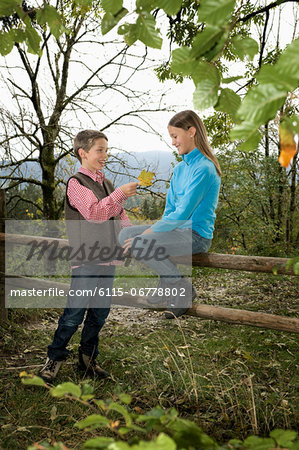 Two Children, Girl Sitting On Fence, Bavaria, Germany, Europe Stock Photo - Premium Royalty-Free, Image code: 6115-06778802