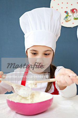 Little girl with chef's hat preparing dough, Munich, Bavaria, Germany Stock Photo - Premium Royalty-Free, Image code: 6115-06966922