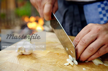 Person Cutting Garlic Stock Photo - Premium Royalty-Free, Image code: 6115-07282738