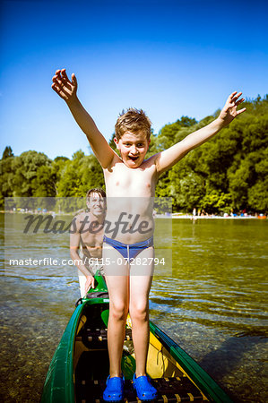 Boy in bathing trunks in a canoe, arms raised, Bavaria, Germany Stock Photo - Premium Royalty-Free, Image code: 6115-07282794