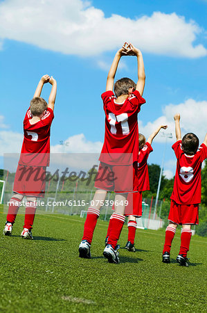 Group of boys at soccer training, stretching, rear view, Munich, Bavaria, Germany Stock Photo - Premium Royalty-Free, Image code: 6115-07539649