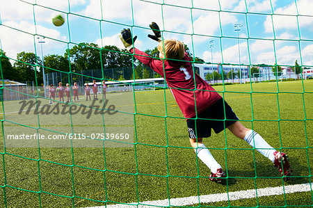 Boys at soccer training, free kick, goal keeper in foreground, Munich, Bavaria, Germany Stock Photo - Premium Royalty-Free, Image code: 6115-07539650