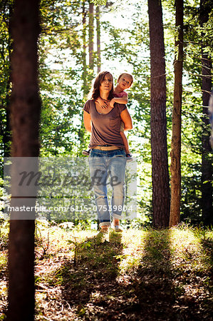 Mother carrying daughter piggyback through forest, Bavaria, Germany Stock Photo - Premium Royalty-Free, Image code: 6115-07539804