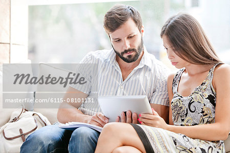 Young couple using digital laptop together Stock Photo - Premium Royalty-Free, Image code: 6115-08101131
