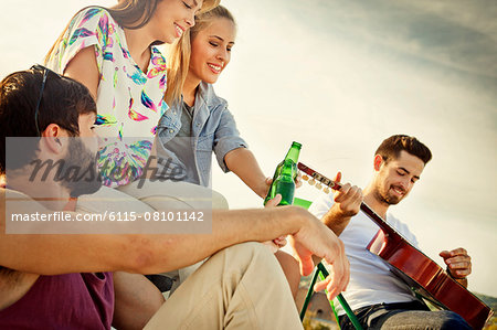 Young people listening to guitarist at rooftop party Stock Photo - Premium Royalty-Free, Image code: 6115-08101142