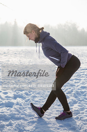 Young woman stretching in snow Stock Photo - Premium Royalty-Free, Image code: 6115-08105183