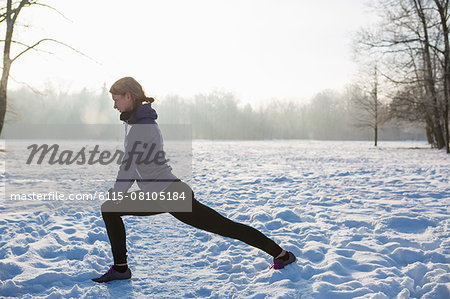 Young woman stretching in snow Stock Photo - Premium Royalty-Free, Image code: 6115-08105184