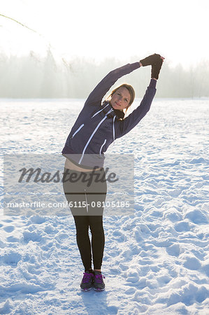 Young woman stretching in snow Stock Photo - Premium Royalty-Free, Image code: 6115-08105185