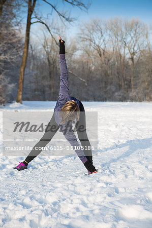 Young woman stretching in snow Stock Photo - Premium Royalty-Free, Image code: 6115-08105186