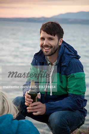 Man on water's edge drinking beer at sunset Stock Photo - Premium Royalty-Free, Image code: 6115-08239654