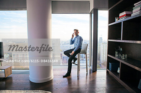 Businessman in apartment on the phone Stock Photo - Premium Royalty-Free, Image code: 6115-08416148