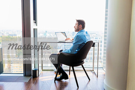 Businessman in apartment using laptop computer Stock Photo - Premium Royalty-Free, Image code: 6115-08416171