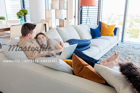 Couple relaxing in modern apartment Stock Photo - Premium Royalty-Free, Image code: 6115-08416183