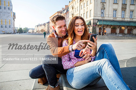 Mid adult couple on a city break using smart phone Stock Photo - Premium Royalty-Free, Image code: 6115-08416248