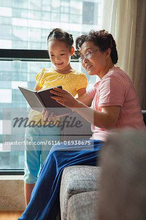 Grandmother reading book to her granddaughter Stock Photo - Premium Royalty-Free, Image code: 6116-06938675