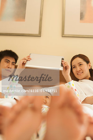Family Using Tablet in Bed Stock Photo - Premium Royalty-Free, Image code: 6116-06938711