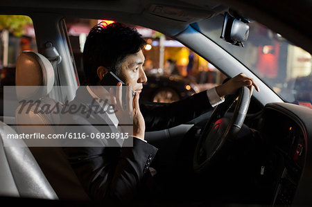 Businessman With Cell Phone In Car Stock Photo - Premium Royalty-Free, Image code: 6116-06938913