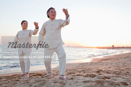 Two older people practicing Taijiquan on the beach at sunset, China Stock Photo - Premium Royalty-Free, Image code: 6116-06939027