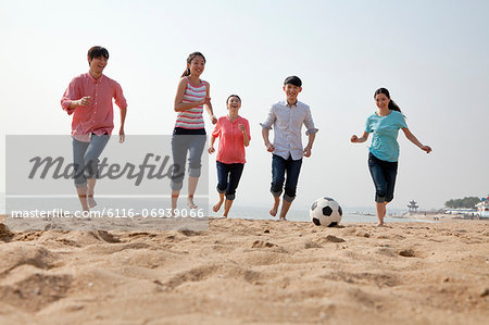 Young Friends Playing Soccer on the Beach Stock Photo - Premium Royalty-Free, Image code: 6116-06939066