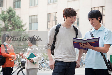 Students discussing and looking at the book, another student talking with professor on the background Stock Photo - Premium Royalty-Free, Image code: 6116-06939103