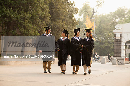 Young Graduates Walking Across Campus Stock Photo - Premium Royalty-Free, Image code: 6116-06939206