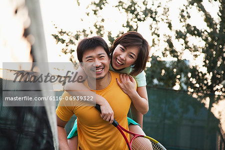 Boyfriend holding his girlfriend next to the tennis net Stock Photo - Premium Royalty-Free, Image code: 6116-06939322