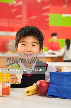 School boy portrait eating lunch in school cafeteria Stock Photo - Premium Royalty-Free, Image code: 6116-06939458