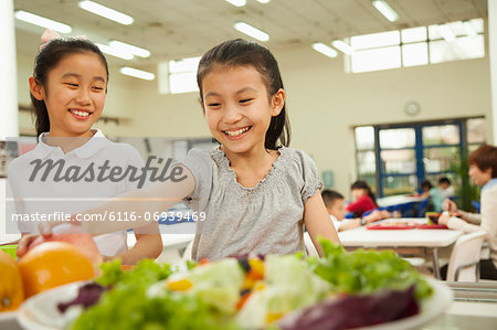 Students reaching for healthy food in school cafeteria Stock Photo - Premium Royalty-Free, Image code: 6116-06939469