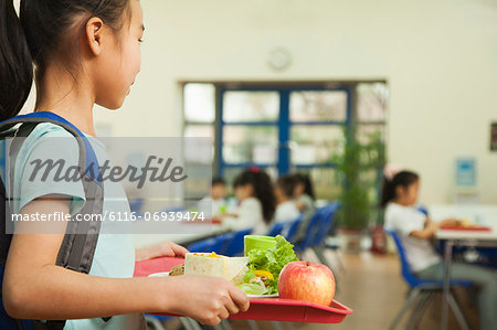 School girl holding food tray in school cafeteria Stock Photo - Premium Royalty-Free, Image code: 6116-06939474