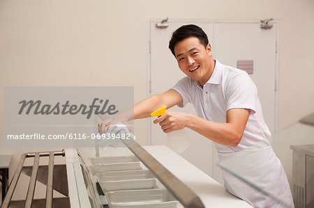 Cafeteria worker cleaning food serving area Stock Photo - Premium Royalty-Free, Image code: 6116-06939482