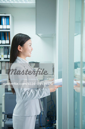Businesswoman Handing Paper Through Doorway Stock Photo - Premium Royalty-Free, Image code: 6116-06939571