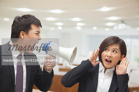 Businessman Talking into Megaphone by Businesswoman's Ear Stock Photo - Premium Royalty-Free, Image code: 6116-07084858