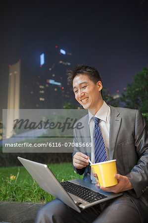Young businessman working outdoors and eating Stock Photo - Premium Royalty-Free, Image code: 6116-07085669