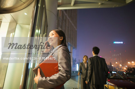 Young businesswoman walking and talking on her cell phone Stock Photo - Premium Royalty-Free, Image code: 6116-07085673