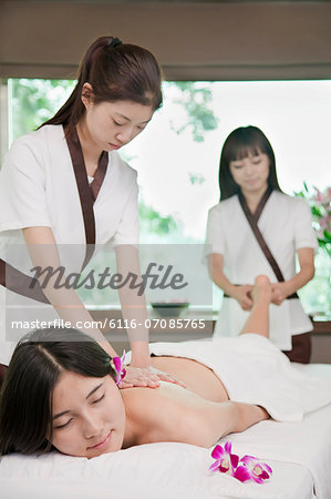 Two Masseuses Massaging One Woman Stock Photo - Premium Royalty-Free, Image code: 6116-07085765