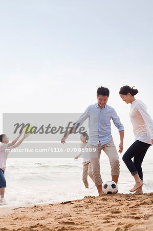 Four young people playing soccer and Frisbee on the beach, China Stock Photo - Premium Royalty-Free, Image code: 6116-07085909