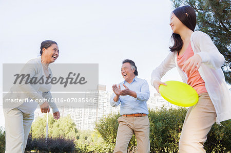 Granddaughter with grandparents playing Frisbee in the park Stock Photo - Premium Royalty-Free, Image code: 6116-07085946