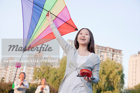 Granddaughter and grandparents with kite in the park Stock Photo - Premium Royalty-Free, Image code: 6116-07085953