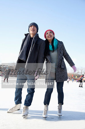 Young couple skating at ice rink Stock Photo - Premium Royalty-Free, Image code: 6116-07086567