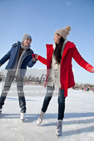 Young couple skating at ice rink Stock Photo - Premium Royalty-Free, Image code: 6116-07086568